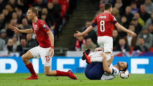 Angličan Eric Dier se svíjí bolestí. Za ním Vladimír Darida, vlevo Tomáš Souček.