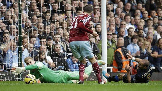 Fotbalista West Hamu Morgan Amalfitano střílí gól brankáři Manchesteru City Hartovi.