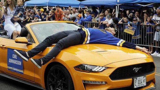 Švéd Carl Gunnarsson oslavuje triumf ve Stanley cupu při sobotním průvodu na kapotě auta.