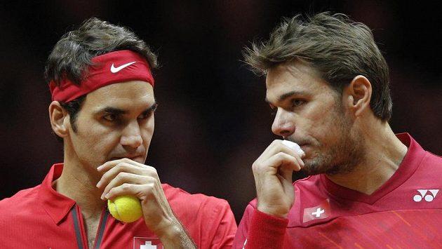 Švýcaři Roger Federer (vlevo) a Stan Wawrinka se radí ve čtyřhře finále Davis Cupu proti Francii.