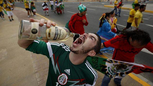 Fanoušek Mexika slaví úspěch svého týmu v duelu proti Brazílii s lahví tequily.