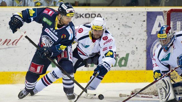 Liberecký Tomáš Bulík (vlevo) bojuje o puk s Martinem Rýglem z Chomutova. Vpravo gólman Pirátů Miroslav Hanuljak.
