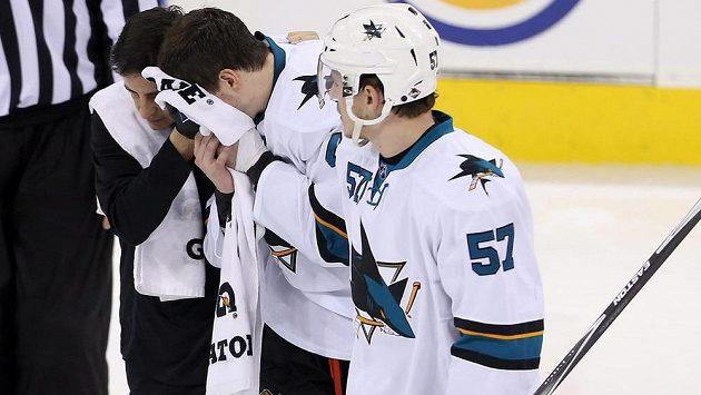 Zraněný útočník San Jose Tomáš Hertl (uprostřed) opouští v doprovodu spoluhráčů ledovou plochu ve Winnipegu.