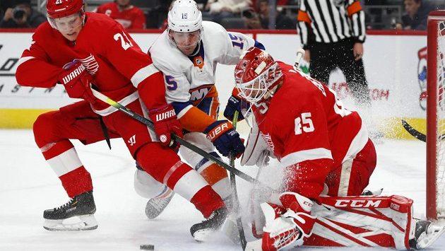 Brankář Detroitu Jonathan Bernier zastavuje za pomoci Dennise Cholowského akci Cala Clutterbucka z New York Islanders.