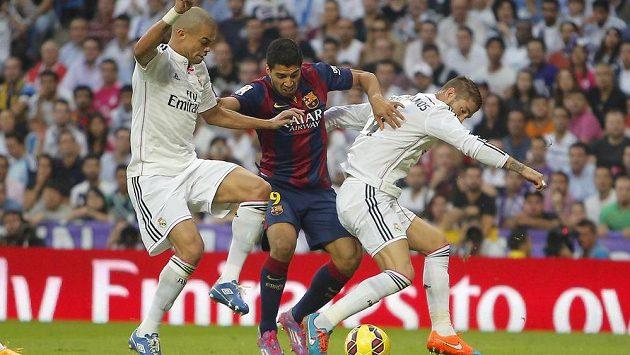 Luis Suárez z Barcelony (uprostřed) se probíjí mezi Pepém (vlevo) a Sergio Ramosem z Realu Madrid.