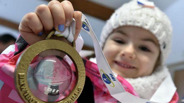 Čtyřletá Kristínka Doležalová z Prahy se zlatou medailí, kterou jí daroval vítěz závodu Martin Fourcade z Francie.