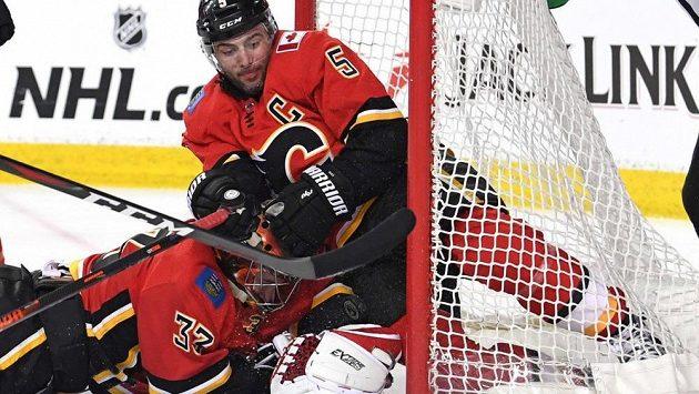 Kapitán Calgary Mike Giordano (vpravo) zaskakuje obětavým zákrokem na brankové čáře za gólmana Flames Davida Ritticha.