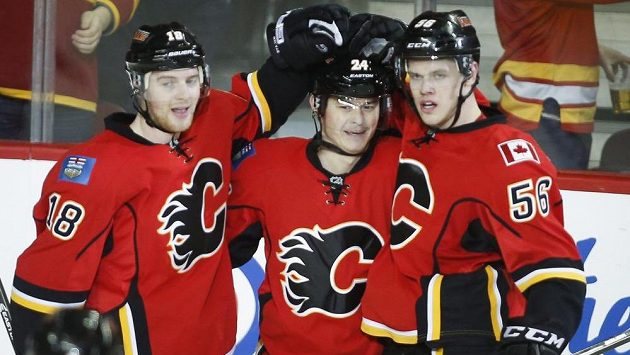 Útočník Calgary Jiří Hudler (uprostřed) se raduje se spoluhráči Mattem Stajanem (vlevo) a Tylerem Wotherspoonem z gólu.