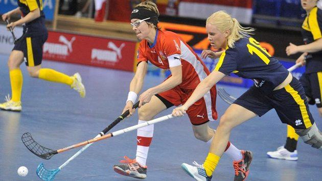 Česká florbalistka Zuzana Macurová (v červeném dresu) v souboji s Amanou Wallovou ze Švédska (druhá zprava).