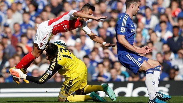 Nepříjemná srážka - brankář Chelsea Thibaut Courtois (ve žlutém) dostal od útočníka Arsenalu Alexise Sáncheze ránu do hlavy.