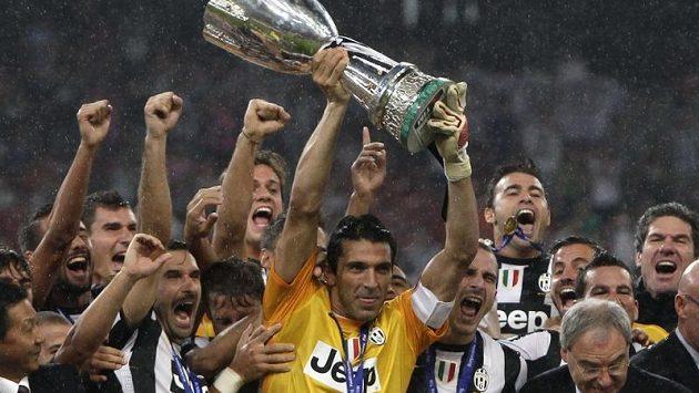 Gólman a kapitán Juventusu Gianluigi Buffon zvedá nad hlavu Superpohár, který jeho tým získal v Pekingu po vítězství nad Neapolí v prodloužení.