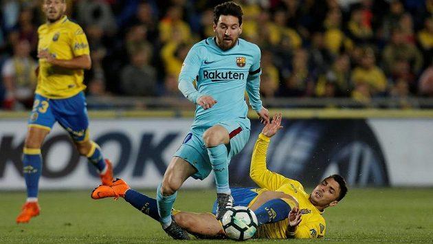 Barcelonský Lionel Messi uniká obránci Las Palmas Ximovi Navarrovi, který ho fauluje.