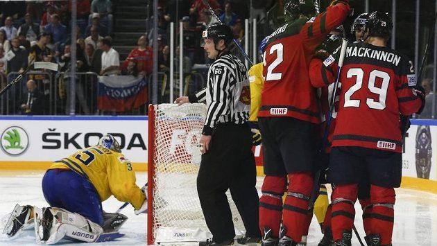 Kanaďané oslavují vyrovnávací branku, gólman Švédska Henrik Lundqvist loví puk z branky.