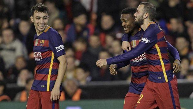 Fotbalisté Barcelony Kaptoum (uprostřed), Munir El Haddadi (vlevo) a Alex Vidal se radují z vyrovnávacího gólu ve Valencii.