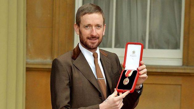 Britský cyklista Braldey Wiggins pózuje před Buckhinghamským palácem s medailí od královny Alžběty II.