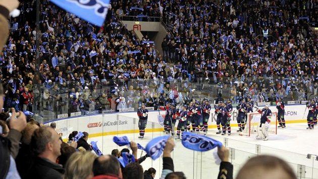 Hokejisté Slovanu slaví s fanoušky vítězství.