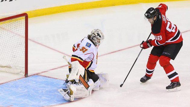 Brankář Calgary Karri Rämö likviduje šanci Ďáblů. Vpravo je útočník New Jersey Jaromír Jágr.
