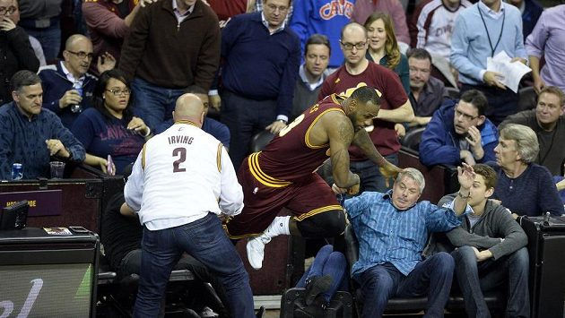 Basketbalista Clevelandu LeBron James padá mezi diváky, kde seděla i manželka golfisty Jasona Daye.