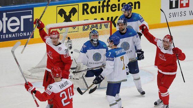 Hokejisté Dánska (v červeném) se radují z branky v zápae proti Kazachstánu.