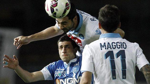 Raúl Albiol z Neapole hlavičkuje míč před Manuelem Pucciarellim z Empoli. Přihlíží Christian Maggio.