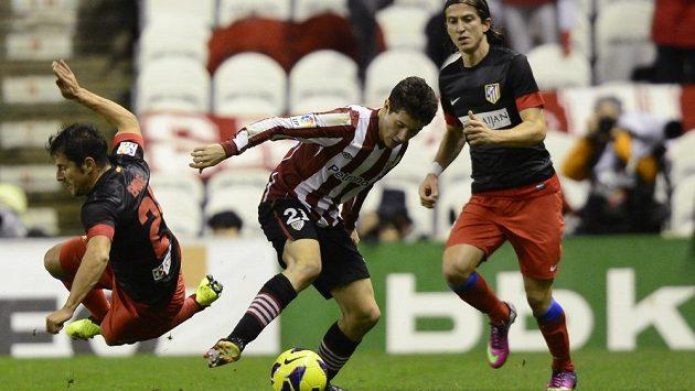 Emre Belözoglu (zcela vlevo) v dresu Atlétika Madrid bojuje o míč s Filipem Luisem Kasmirskim z Bilbaa.