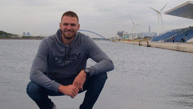 Skifař Ondřej Synek, za ním olympijský kanál v Tokiu i s větrnými turbínami.