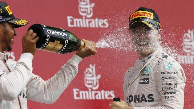 """Lewis Hamilton """"sprchuje"""" šampaňským svého týmového kolegu Nica Rosberga."""