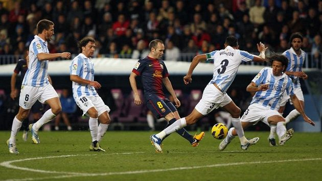 Fotbalisté Malagy v utkání proti Barceloně. Obránce Weligton (s číslem 3) se snaží společně se spoluhráči zastavit hostujícího záložníka Iniestu.