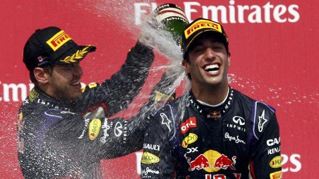 """Sebastian Vettel (vlevo) připravil svému stájovému kolegovi z Red Bullu a vítězi Velké ceny Kanady Danielu Ricciardovi """"povinnou koupel"""" v šampaňském."""