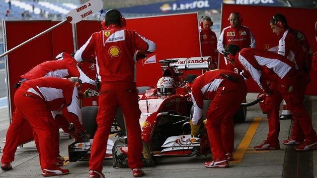 Sebastian Vettel v péči mechaniků Ferrari při testech v Jerezu.