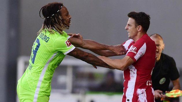 Fotbalista Wolfsburgu Kevin Mbabu v souboji se Santiagem Ariasem z Atlétika Madrid na ilustračním snímku.