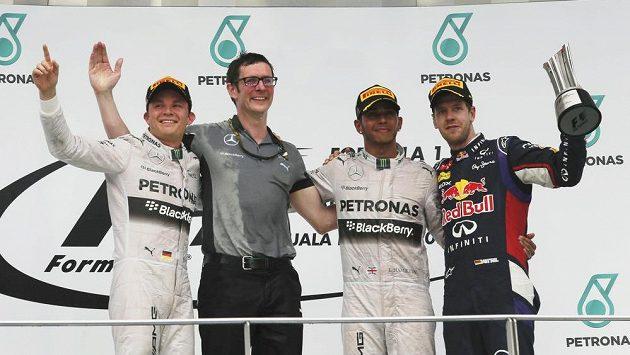 Pilot Nico Rosberg, šéfinženýr Mercedesu Andrew Shovlin, Lewis Hamilton a Sebastian Vettel z Red Bullu na stupních vítězů v Malajsii.