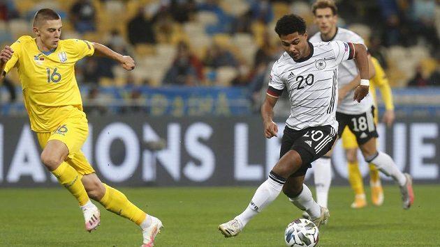 Fotbalovým kouzlům Serge Gnabryho (vpravo) z Německa přihlíží Ukrajinec Vitalij Mykolenko.
