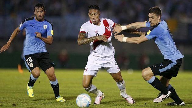 Peruánec Paolo Guerrero na snímku z loňského utkání mezi Uruguayci Sebastianem Coatesem a Alvarem Gonzalezem.