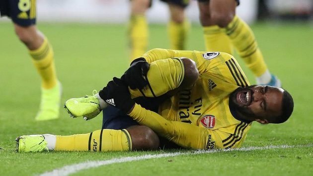 Zraněný útočník Alexandre Lacazette z Arsenalu se svíjí na trávníku.