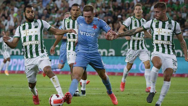 Útočník Slavie Jan Kuchta se snaží prosadit mezi dvěma bránícími hráči Ferencvároše Budapešť ve třetím předkole Ligy mistrů.