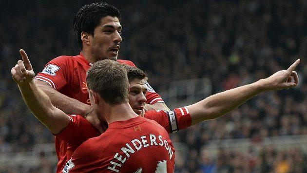 Liverpoolský Steven Gerrard (vpravo) oslavuje spolu s Luisem Suarezem (nahoře) a Jordanem Hendersonem svůj 100. gól v Premier League.