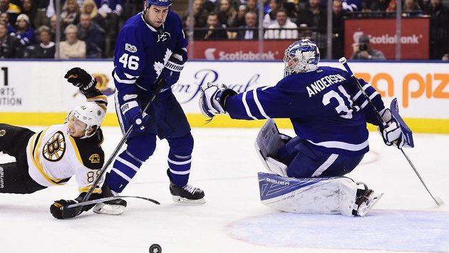 Útočník Bostonu Bruins David Pastrňák (88) padá k zemi po souboji se svým krajanem Romanem Polákem z Toronta v utkání NHL, které Boston prohrál 2:4.