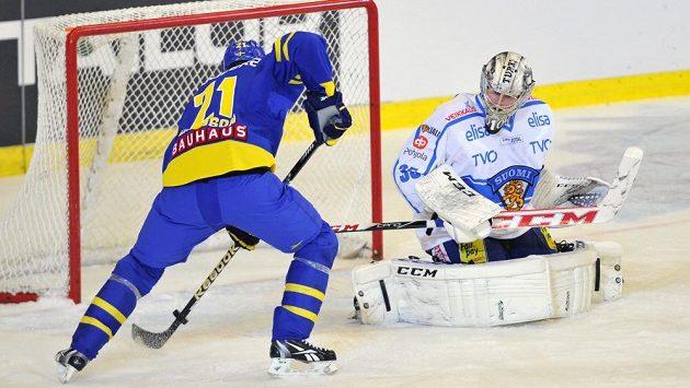 Jimmie Ericsson ze Švédska střílí gól. Vpravo finský brankář Atte Engren.