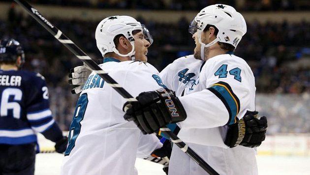 Obránce San Jose Marc-Edouard Vlasic (vpravo) a útočník Žraloků Joe Pavelski slaví gól na ledě San Jose.