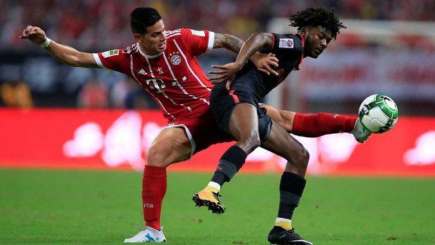 Letní akvizice Bayernu James Rodríguez (vlevo) v souboji s Ainsleym Maitlandem-Nilesem z Arsenalu.