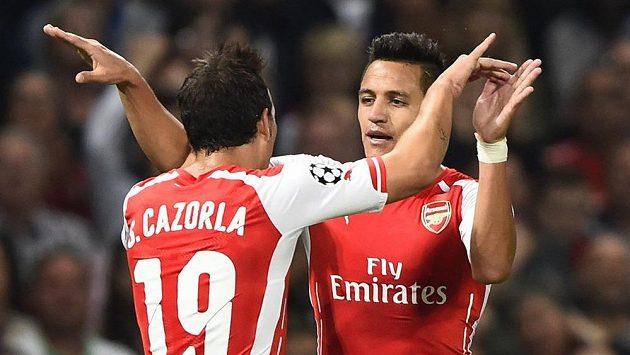 Fotbalisté Arsenalu Santi Cazorla (vlevo) a střelec Alexis Sánchez se radují z branky proti Besiktasi Istanbul.