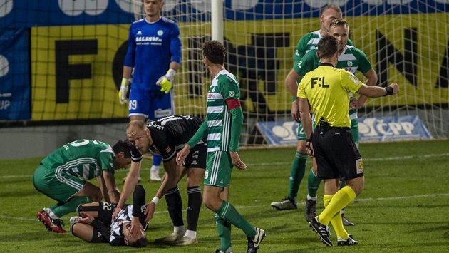 Záložník Budějovic Karol Mészáros leží na trávníku po faulu záložníka Bohemians Kamila Vacka. Rozhodčí Ondřej Pechanec odpískal penaltu.