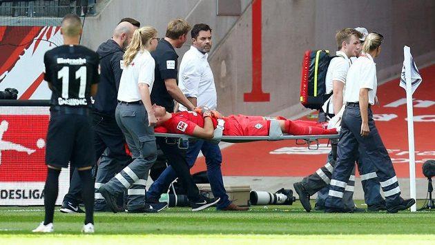Zraněný brankář Brém Jiří Pavlenka opouští stadión Franfurtu na nosítkách.