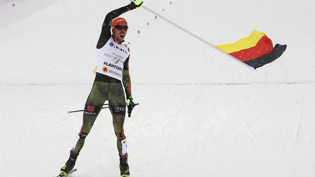 Finišman německé sdruženářské štafety Johannes Rydzek mává vlajkou v cíli.
