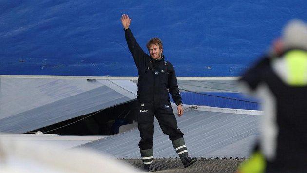 Francois Gabart mává ze své jachty po vylepšení světového rekordu v sóloplavbě kolem světa.