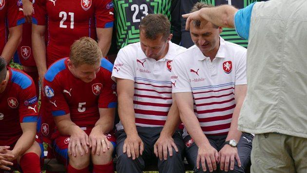 Zprava trenéři Jan Suchopárek a Petr Kouba zaučují kapitána Jakuba Brabce, jak předpisově položit ruce na kolena...