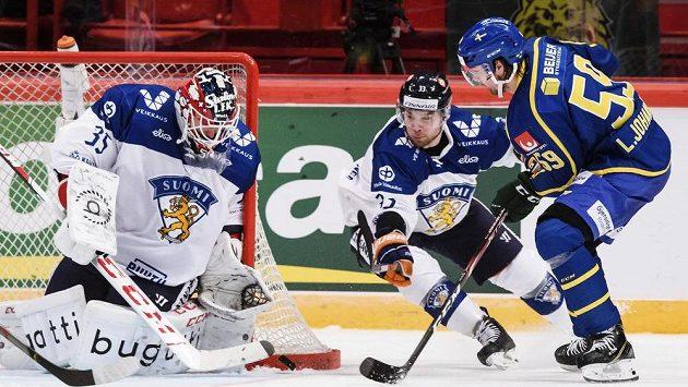 Proti střele švédského hokejisty Linuse Johanssona zasahuje finský brankář Frans Tuohimaa.