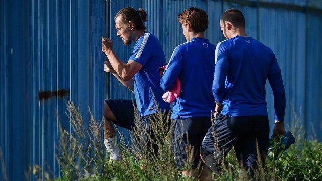 Liberecký obránce Ondřej Švejdík (vlevo) a jeho spoluhráči přichází dírou v plotě na trénikové hřiště před zápasem 1. kola základní skupiny EL proti Braze.
