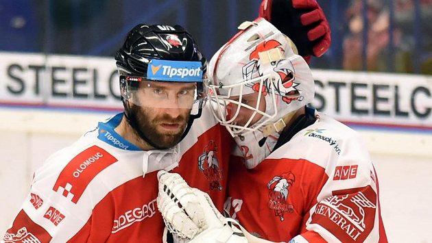 Zleva Martin Vyrůbalík a brankář Branislav Konrád z Olomouce se radují z vítězství na ledě Vítkovic.